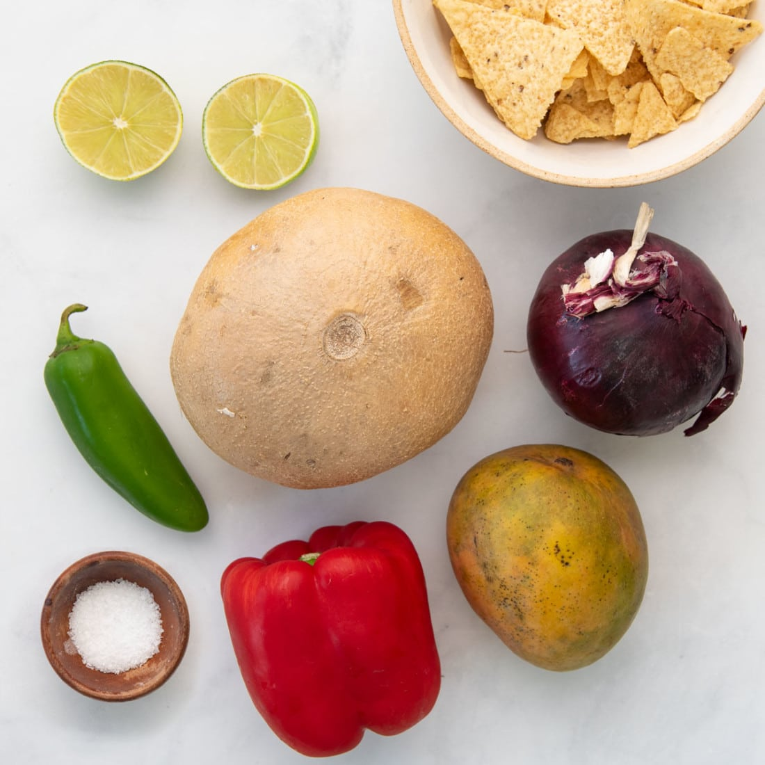 fresh produce, salt, and chips on a white background