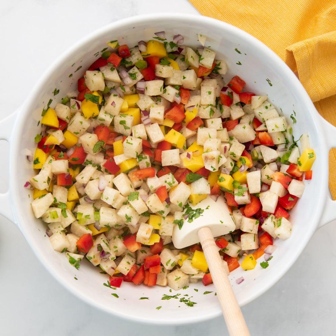 bowl with combined jicama salsa and a spatula