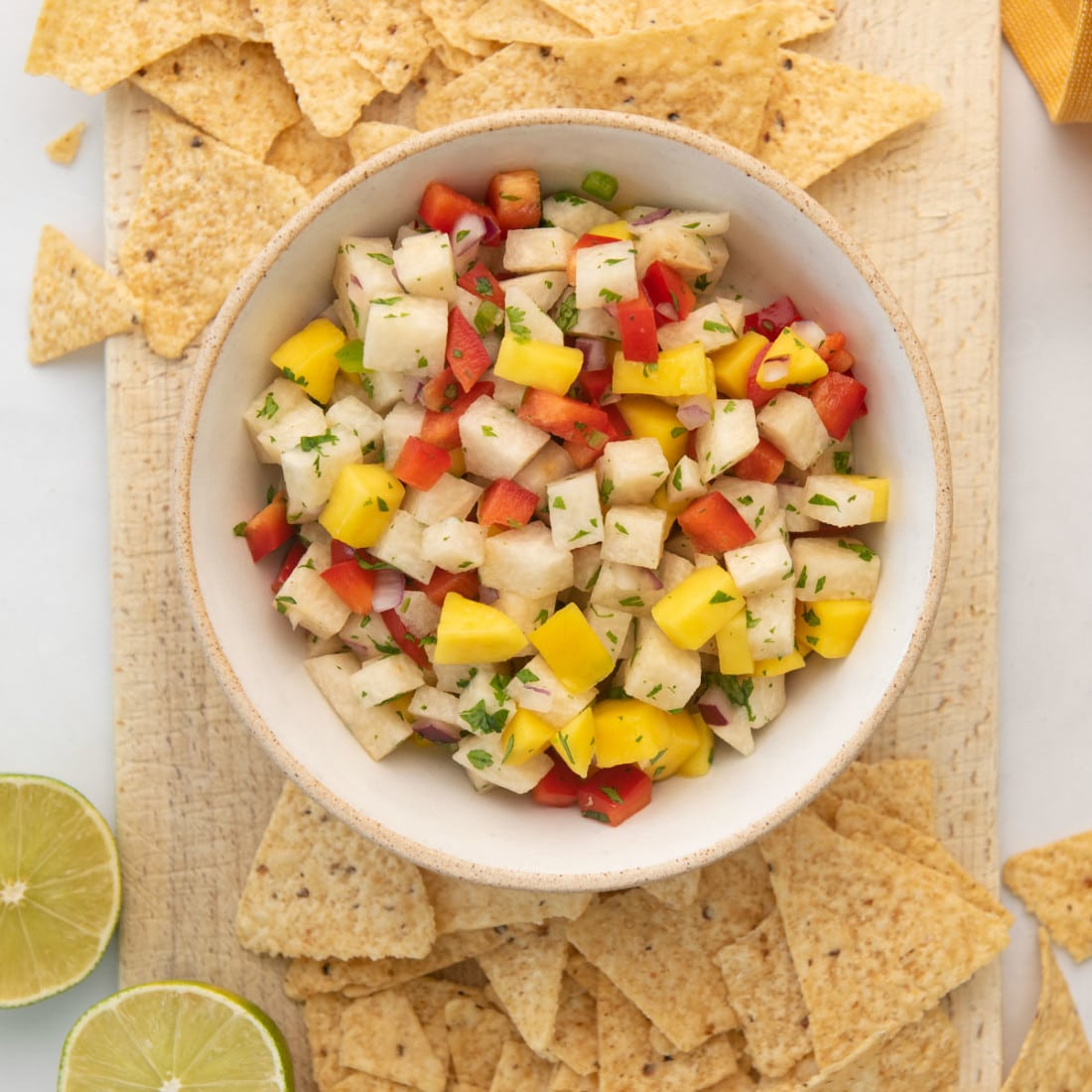 finished bowl of jicama mango salsa on a board surrounded by tortilla chips