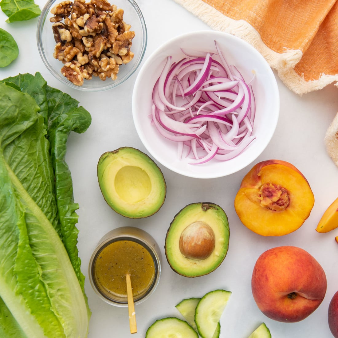 lettuce, avocado, peaches, red onion, walnuts, cucumber, and dressing on white background