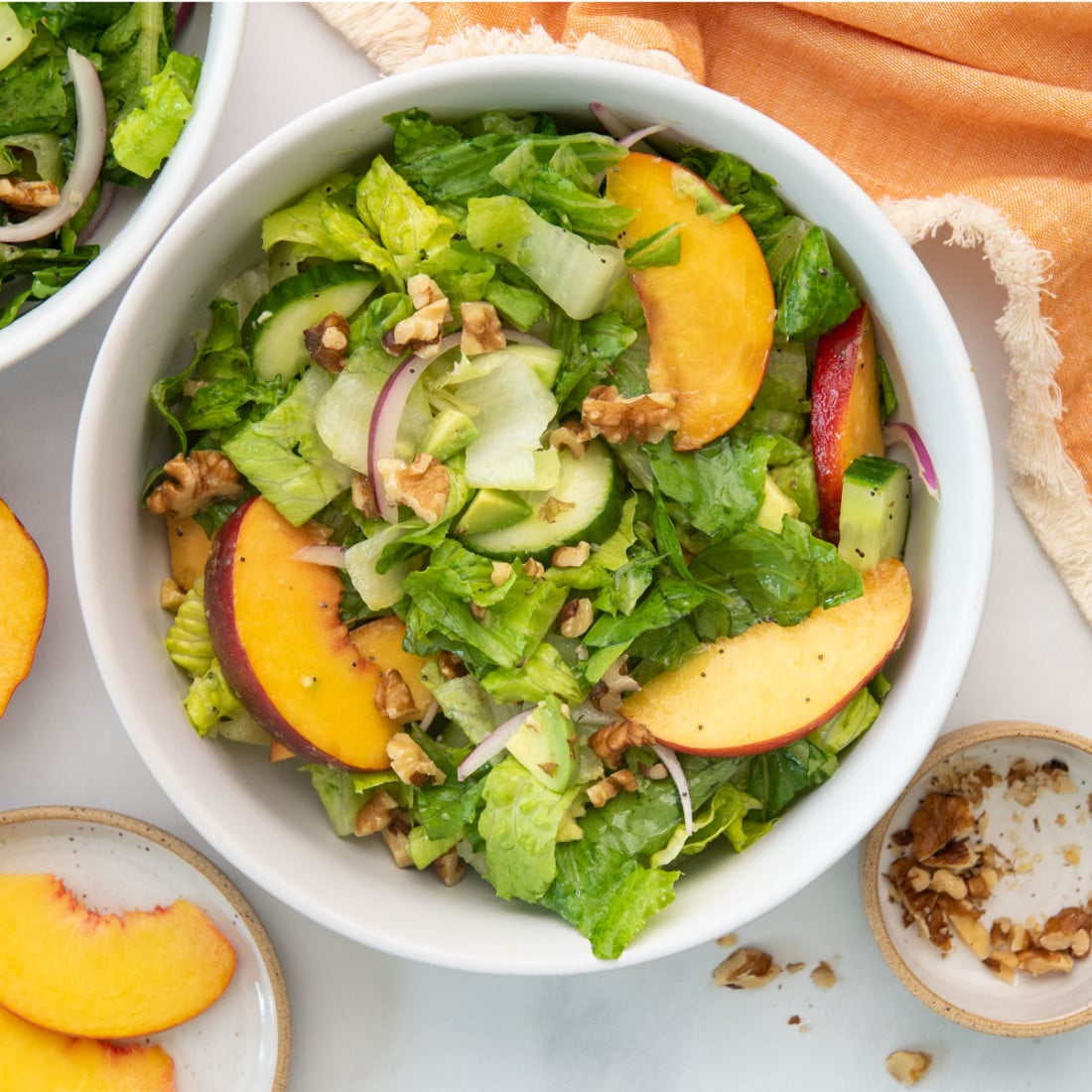 overhead view of salad with peaches and walnuts