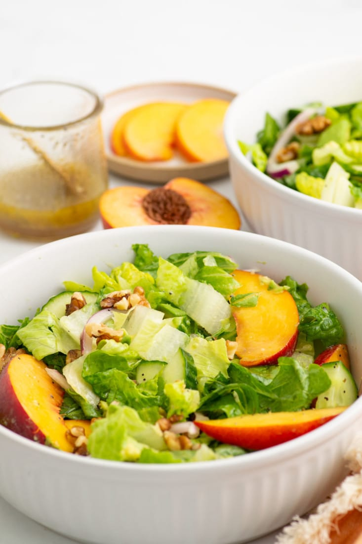 salad with peaches and walnuts in white bowl. dressing is in the background