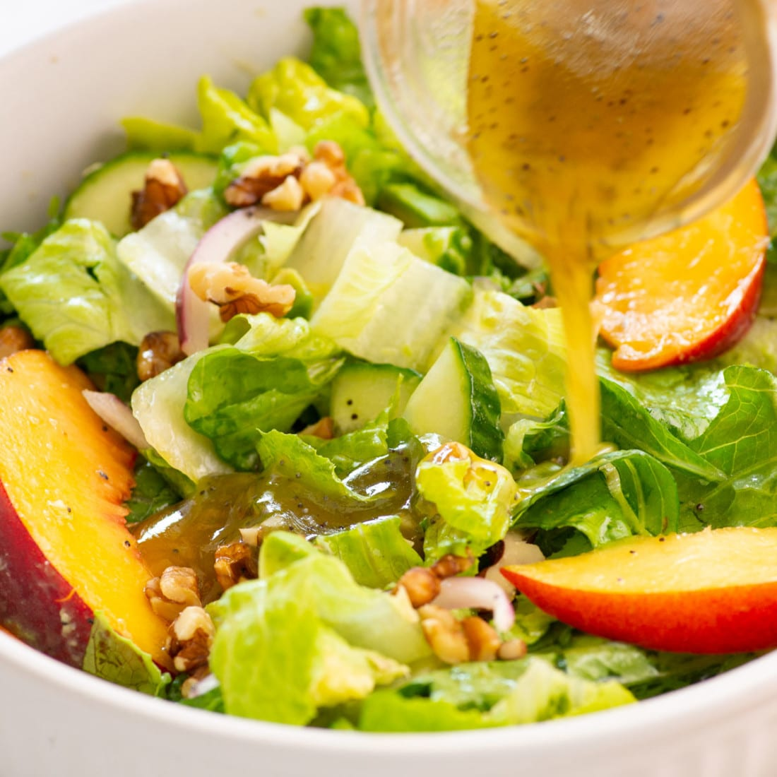 pouring dressing on top of green salad