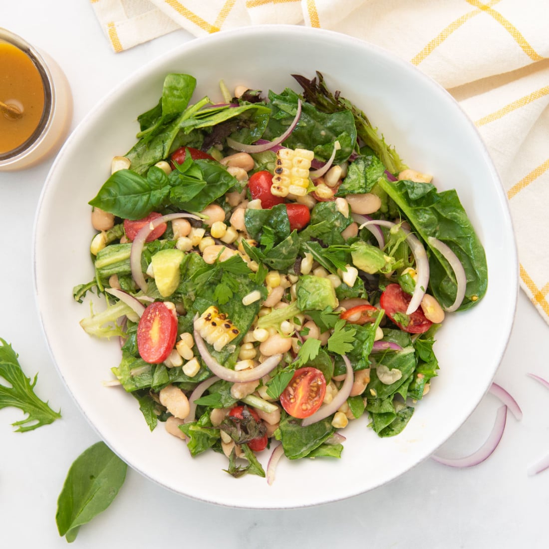 overhead view of salad with greens, grilled corn, tomatoes, beans, red onion, and avocado