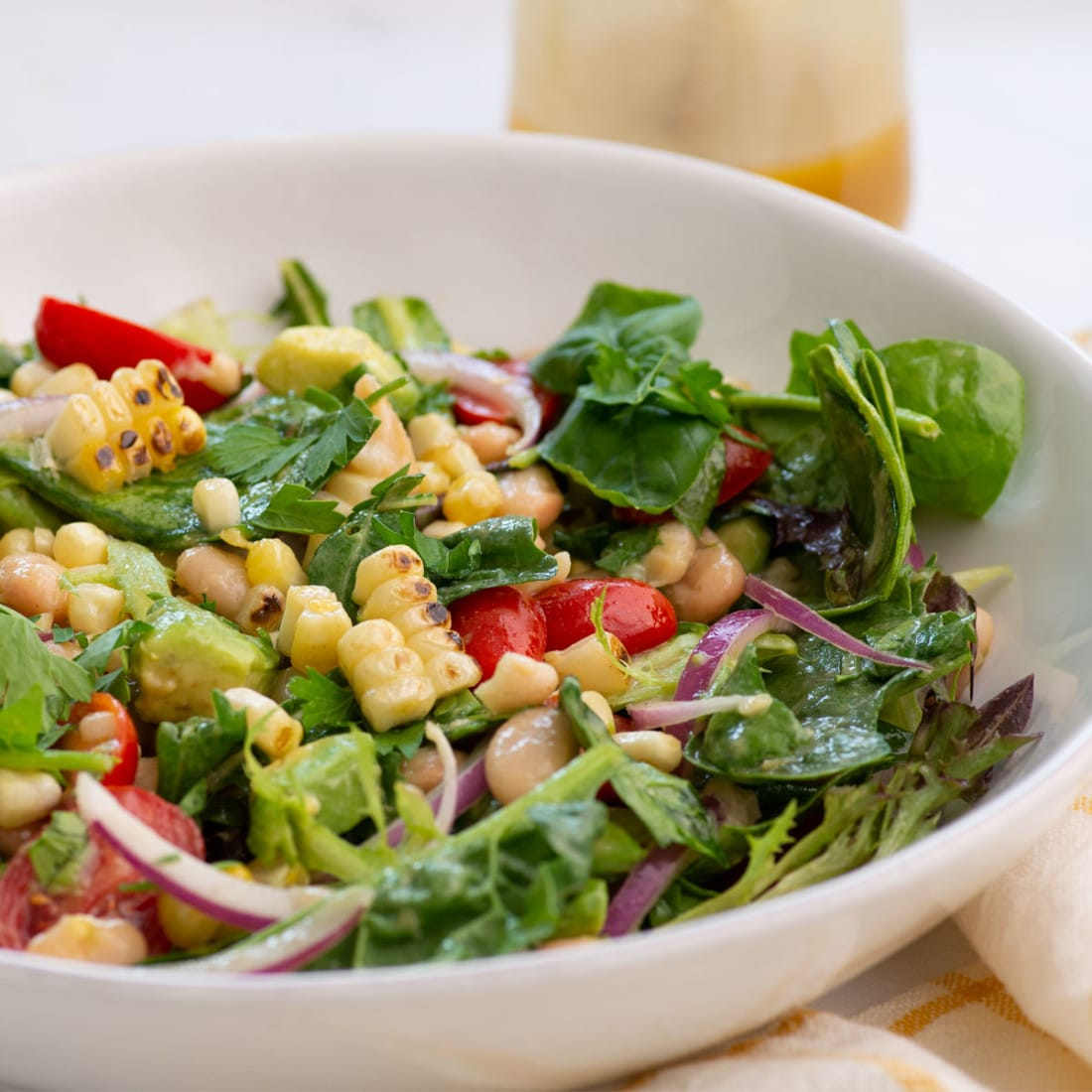 closeup of salad with grilled corn, tomatoes, beans, avocado, and red onion.