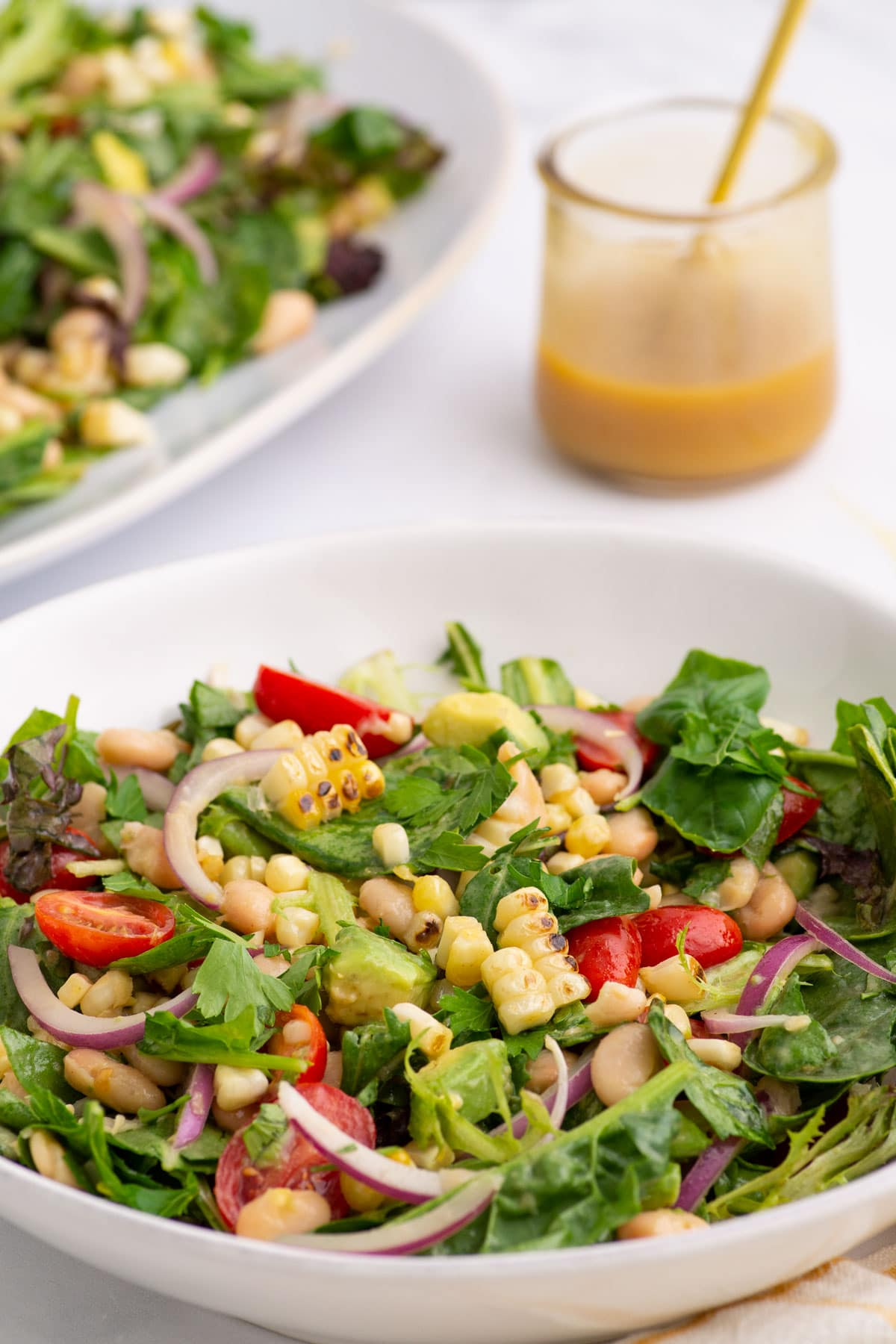 closeup of salad with grilled corn, tomatoes, beans, avocado, and red onion. honey mustard dressing in background