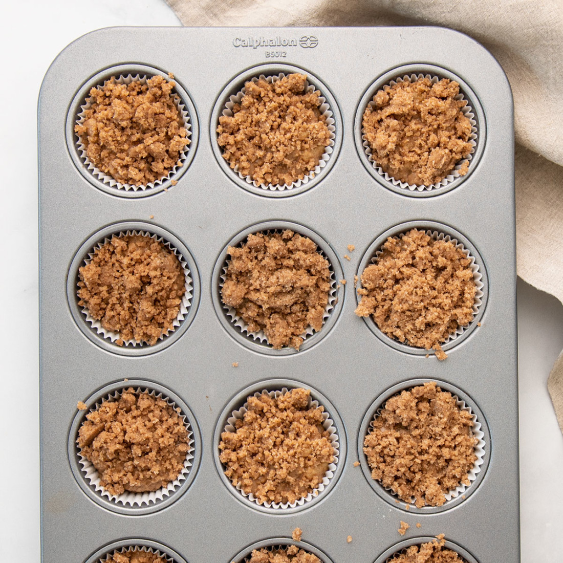 muffin tin filled with batter and topped with streusel crumble