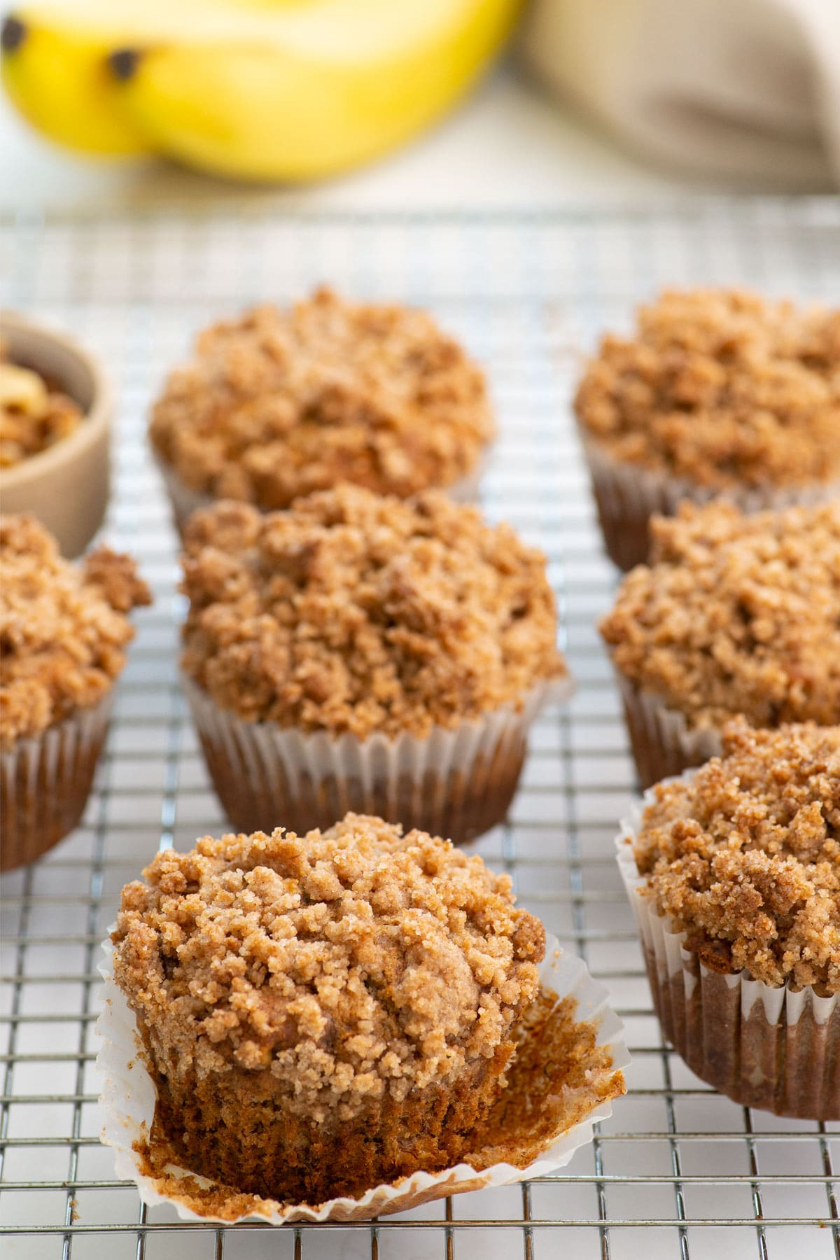side view of vegan banana muffins with crumbly topping on a cooling rack