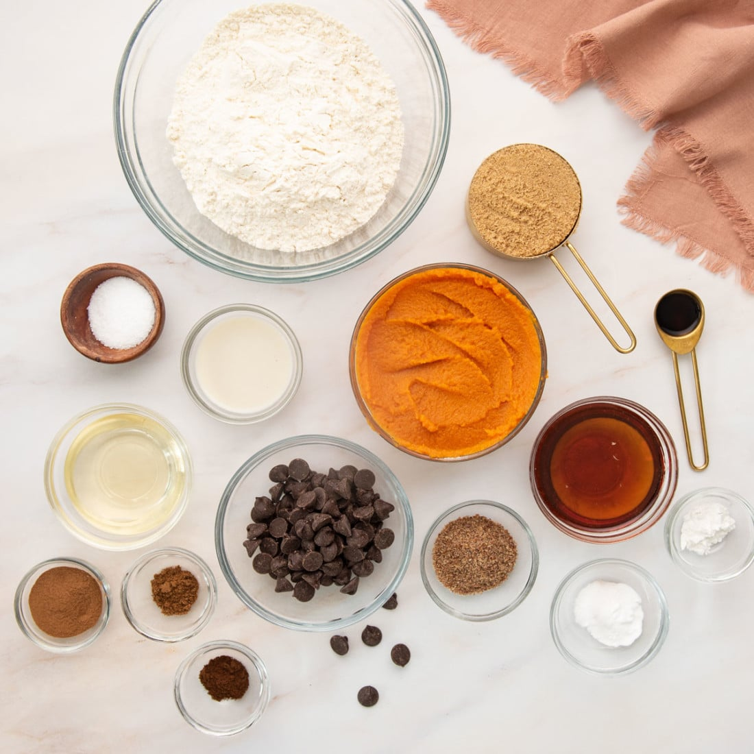 overhead shot of ingredients on a white background: pumpkin puree, flour, sugar, vanilla, spices, flax egg, chocolate chips