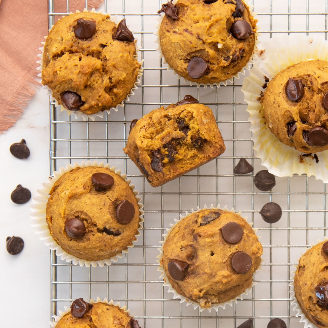 overhead view of chocolate chip muffins made with pumpkin and flax egg, on a wire rack and sprinkles of chocolate chips all around