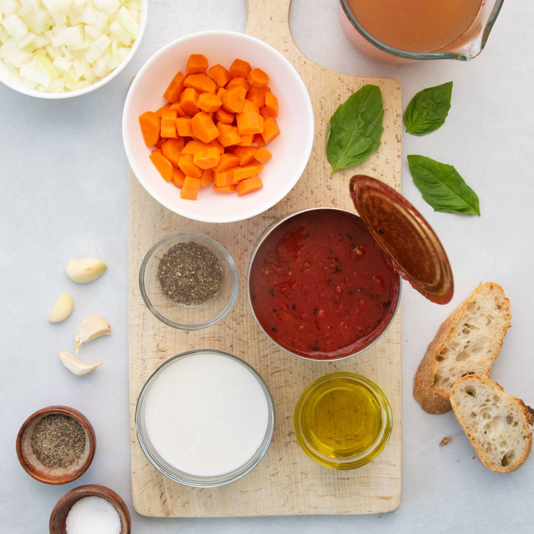 overhead view of canned tomatoes, carrots, coconut milk, seasonings, and bread