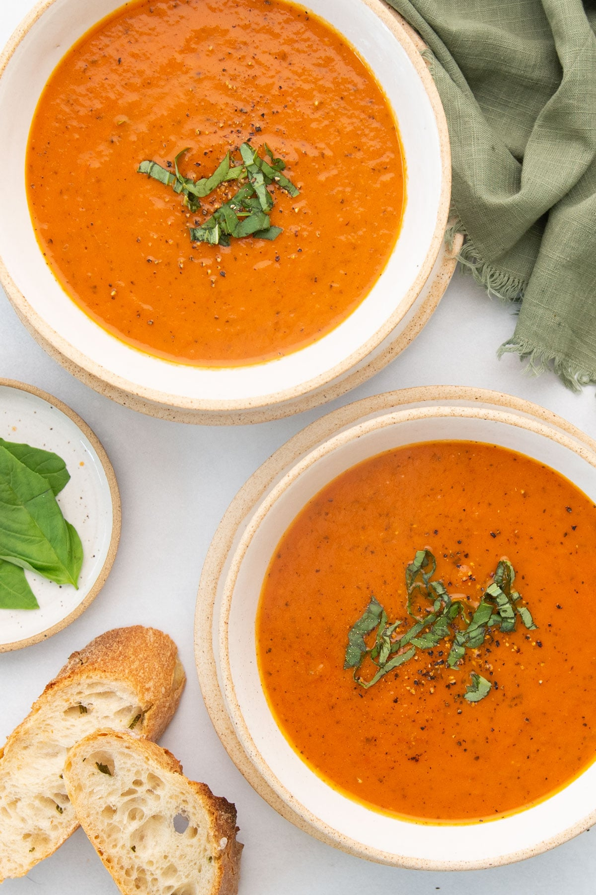 top view two bowls of dairy free tomato soup with basil and slices of bread on the side