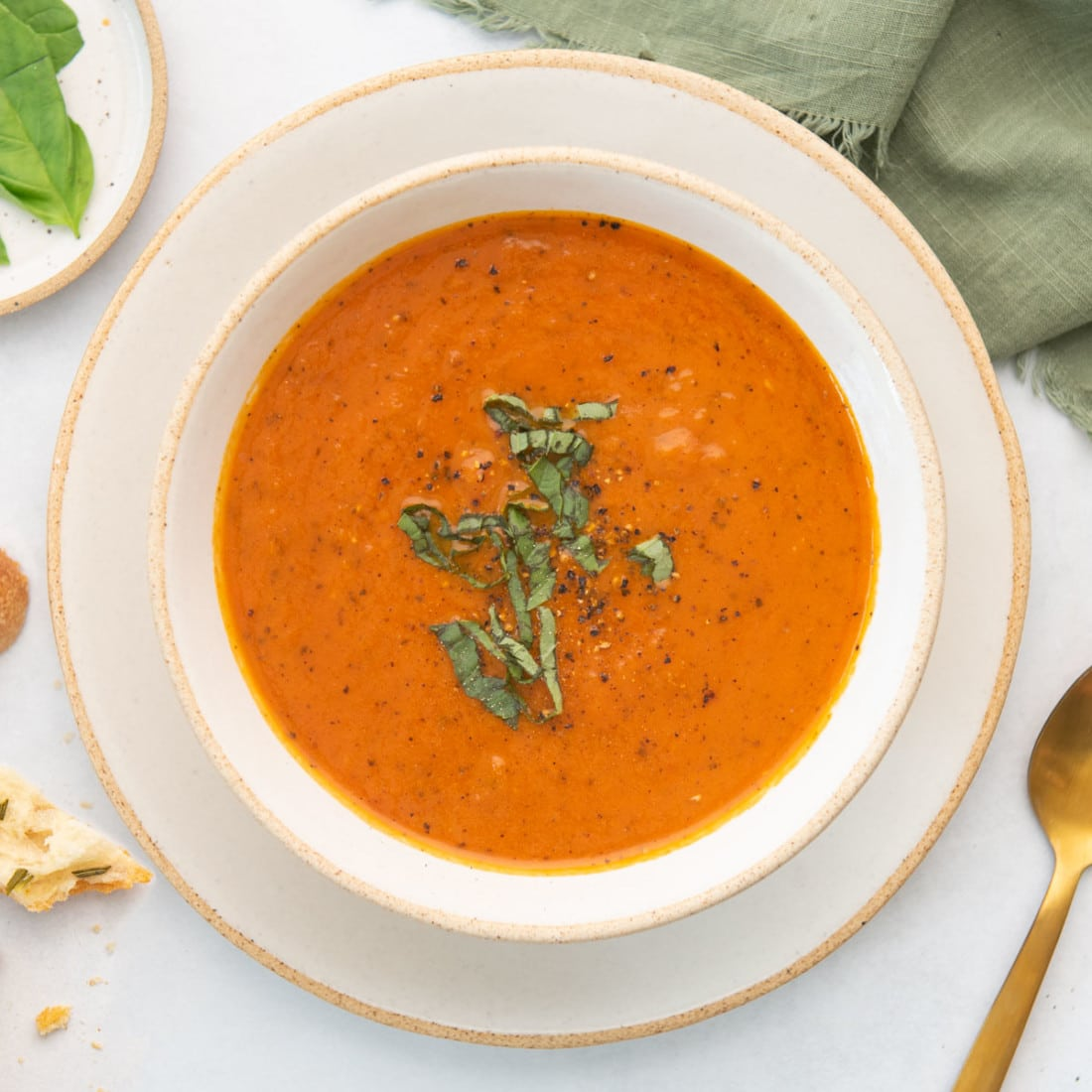 overhead view of plated bowl of creamy tomato soup, topped with slivers of fresh basil and cracked black pepper, with gold spoon on the side