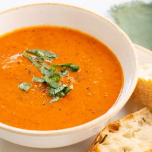 up close view of a bowl of creamy vegan tomato soup with fresh basil slivers