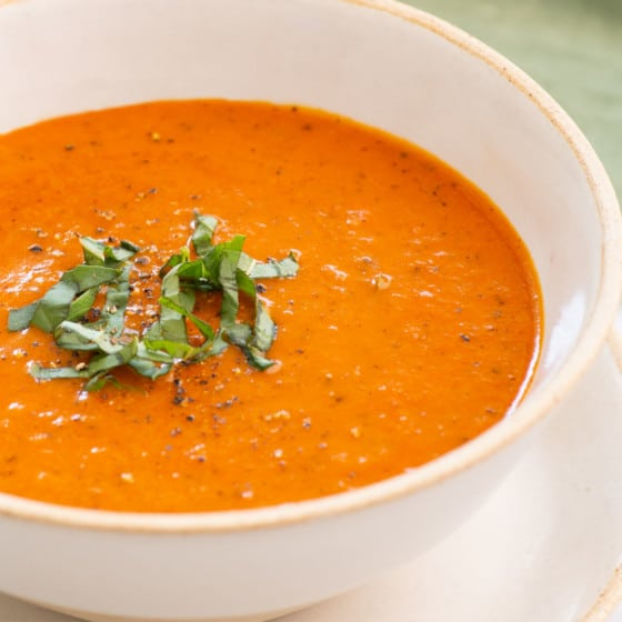 close up side view of a bowl of soup with tomato, carrots, aromatics and topped with fresh basil shreds