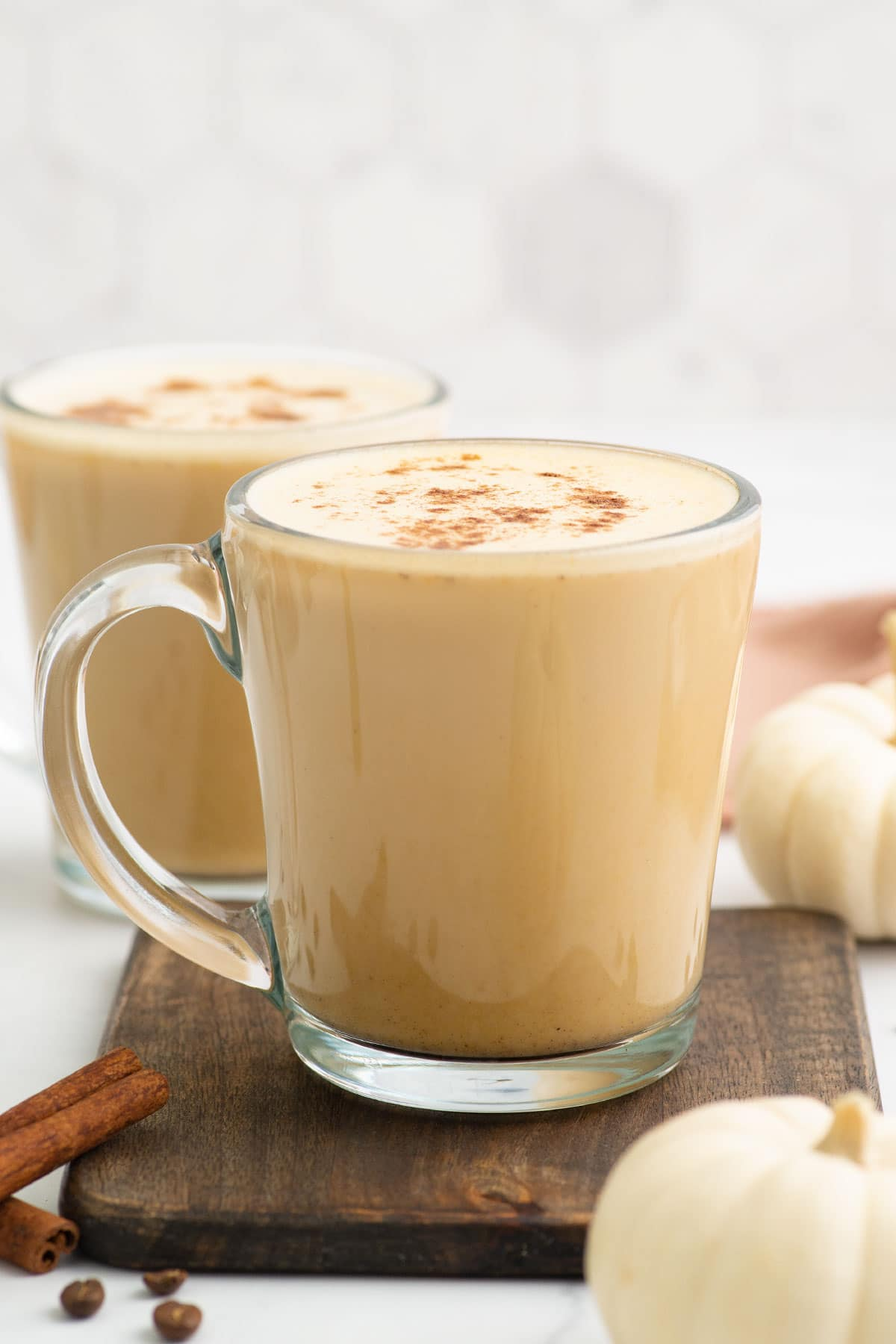 two pumpkin spice lattes on wood board with white mini pumpkins in background.