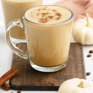 vegan pumpkin spice latte in clear glass mug topped with cinnamon