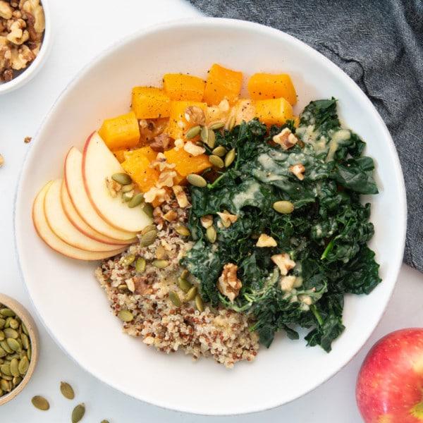 vegan grain bowl with quinoa, butternut squash, apples, kale, walnuts, and pepitas