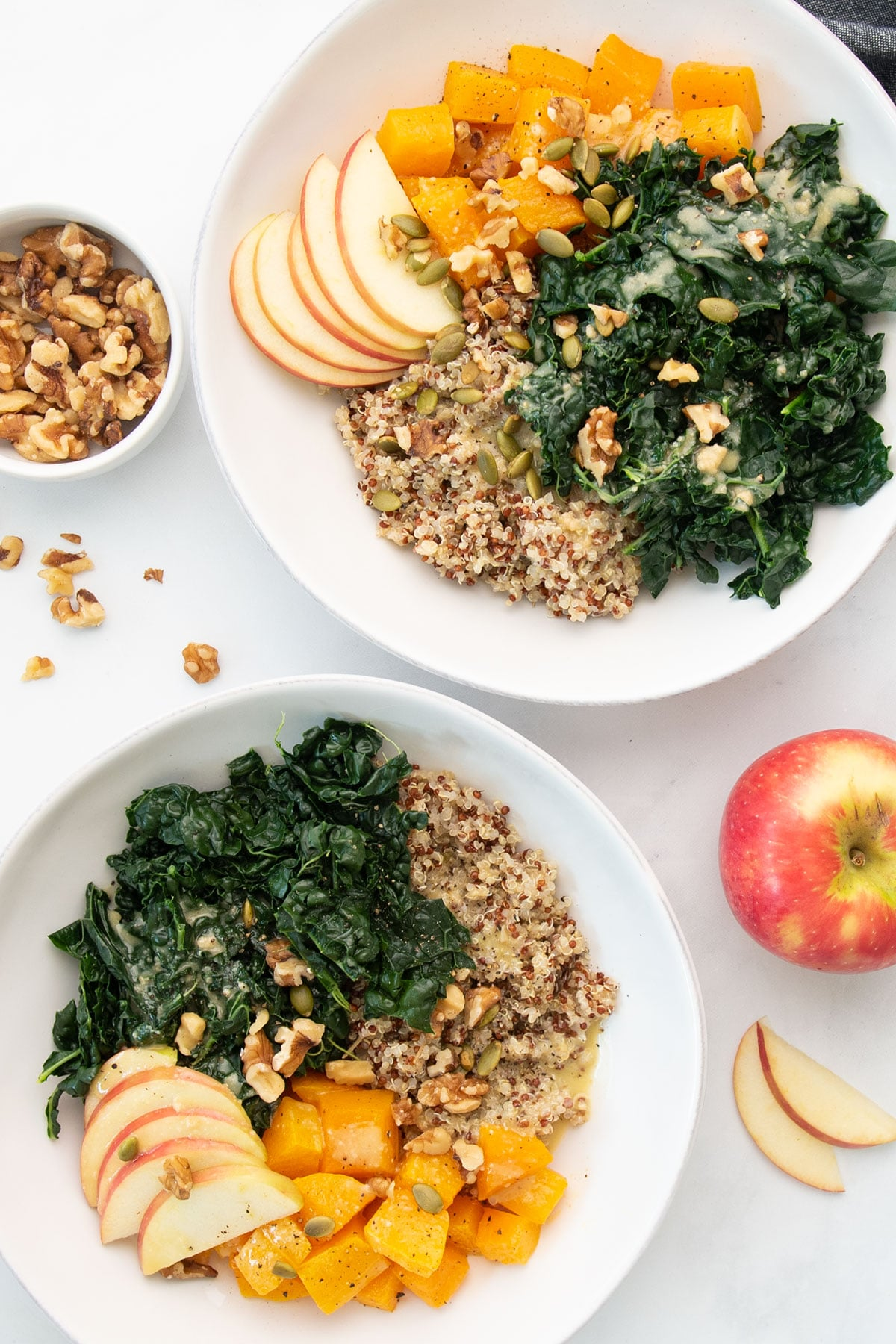 two grain bowls with quinoa, kale, squash, and apples on white background