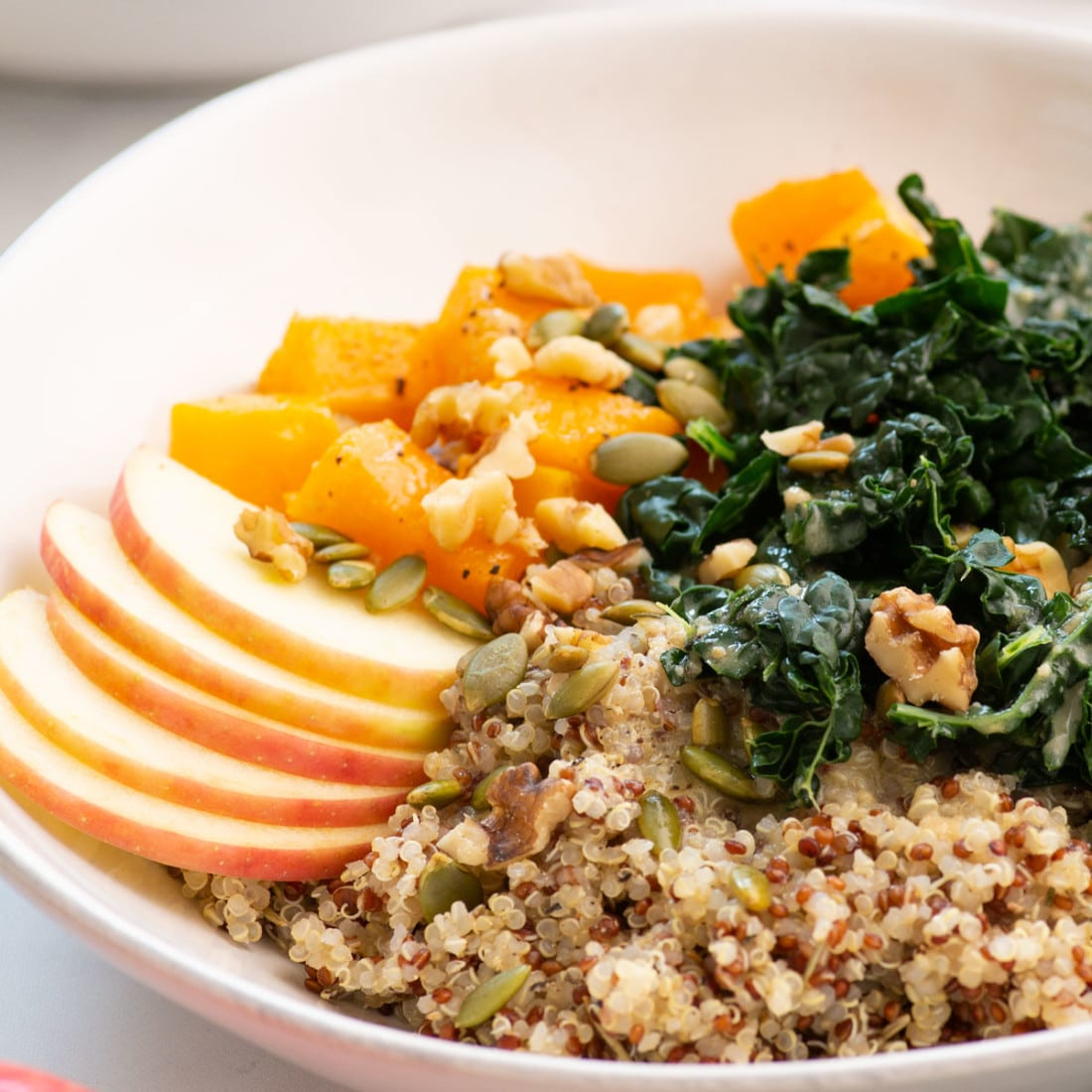 side view of grain bowl with quinoa, kale, apples, squash, pepitas, and walnuts