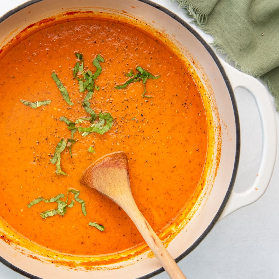 pot of tomato soup with wooden spoon